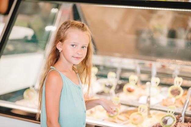 Garoto bonito desfrutando de sorvete italiano real perto de gelateria em roma