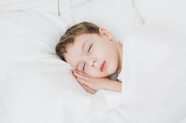 Garoto bonito dorme de manhã na cama
