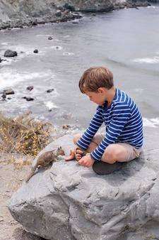 Garoto bonito e corajoso alimentando um esquilo com nozes em um fundo de uma bela paisagem montanhosa