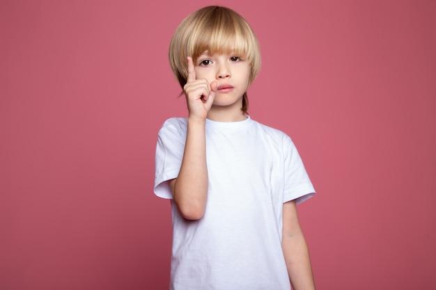 Garoto bonito em camiseta branca adorável criança na parede rosa