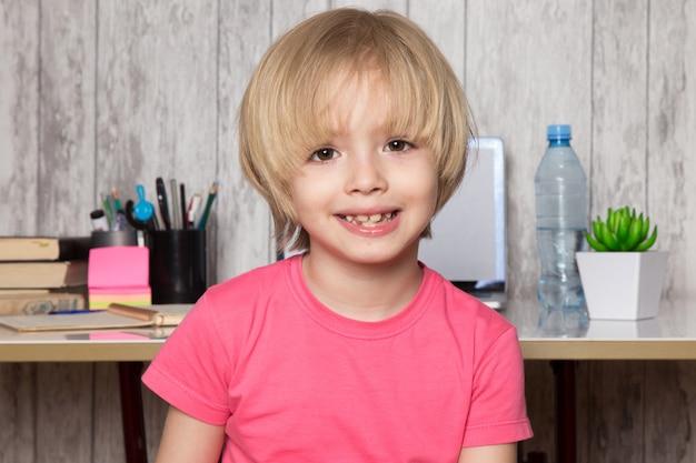 Garoto bonito em camiseta rosa sorrindo em casa