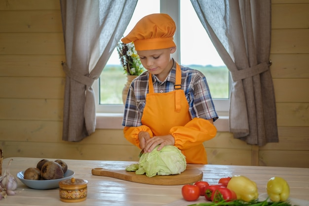 Garoto bonito em um chef de terno laranja corta o repolho para a sopa de vegetais na mesa em uma casa de campo no fundo da janela