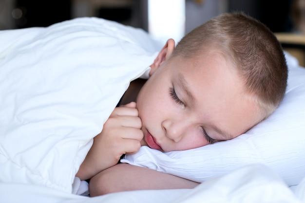 Garoto bonito em uma cama branca sob um cobertor branco