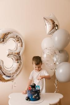 Garoto bonito está comemorando seu aniversário e comendo um delicioso bolo lindo