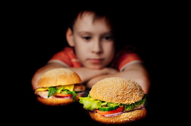 Garoto bonito está sentado na frente de hambúrgueres e pensando em comê-los no preto