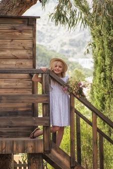 Garoto bonito feliz brincando na casa da árvore no verão, feliz verão na zona rural, parque ecológico