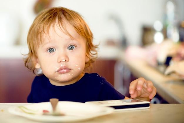 Garoto bonito garoto comendo iogurte e brincar com o telemóvel