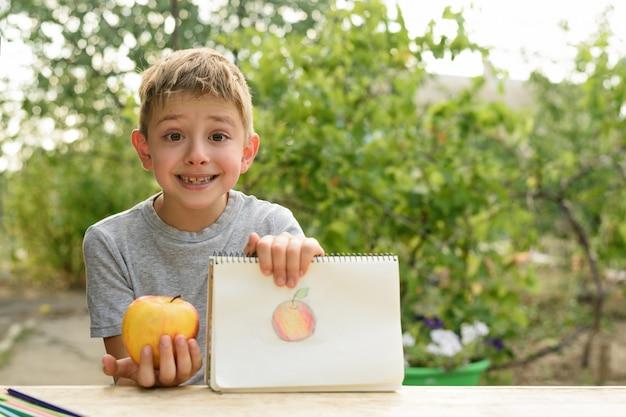 Garoto bonito mostra maçã desenhada. ar livre. jardim no. criativo .