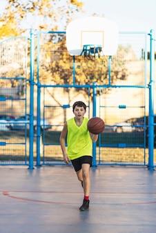 Garoto bonito na camisa amarela joga basquete no recreio da cidade adolescente ativo, desfrutando de jogo ao ar livre com ...