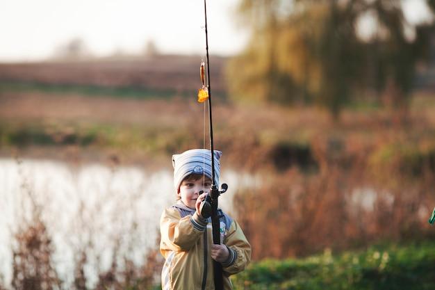 Garoto bonito pesca perto do lago