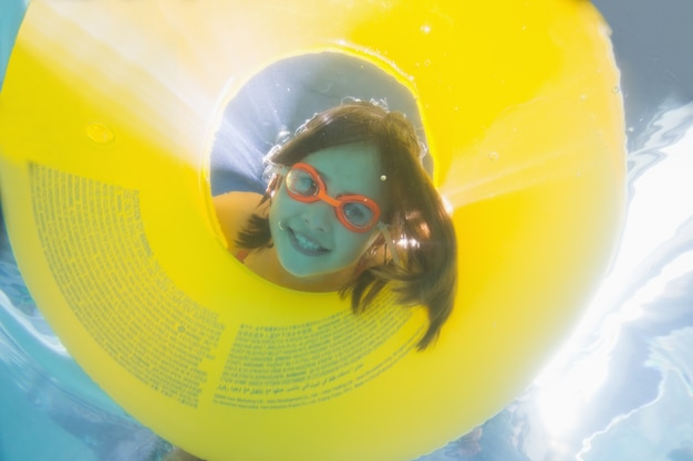 Garoto bonito posando debaixo d'água na piscina no centro de lazer