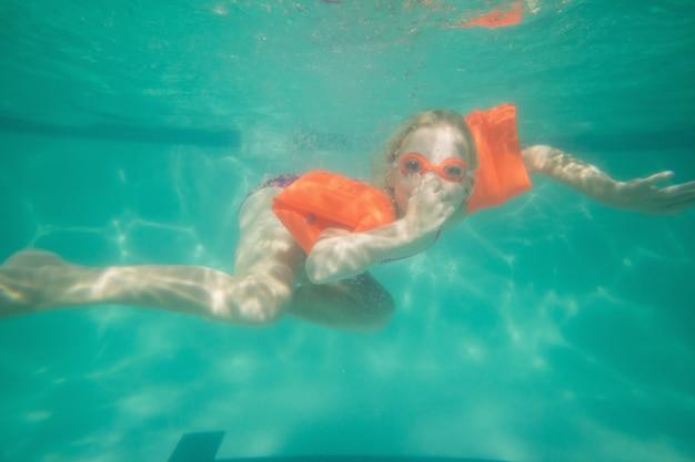 Garoto bonito posando debaixo d'água na piscina