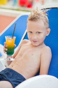 Garoto bonito relaxante num dia quente de verão com bebida cocktail