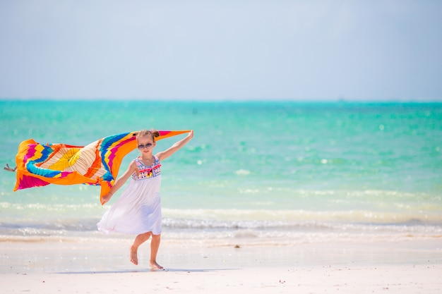 Garoto bonito se divertindo correndo com pareo na praia tropical