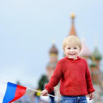 Garoto bonito segurando bandeira russa com e vasilevsky descida no fundo