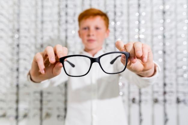 Garoto bonito segurando óculos preto na loja de óptica