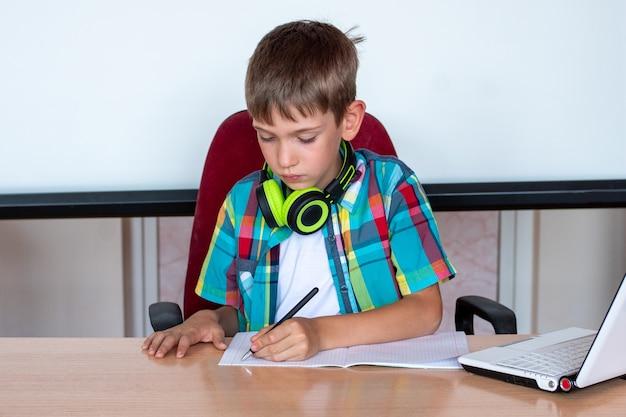 Garoto bonito sentado à mesa, olhando em um caderno, escrevendo a lição de casa ou se preparando para um exame