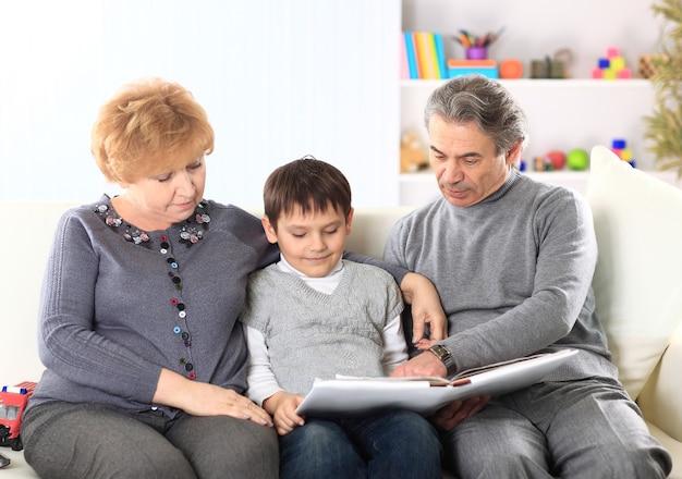 Garoto bonito sentado no colo dos avós e olhando felizes juntos para um álbum de fotos