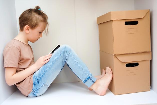Garoto bonito sentado no guarda-roupa lendo um livro
