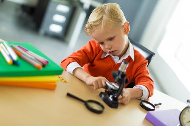 Garoto bonito sentar na mesa do escritório, segure o microscópio