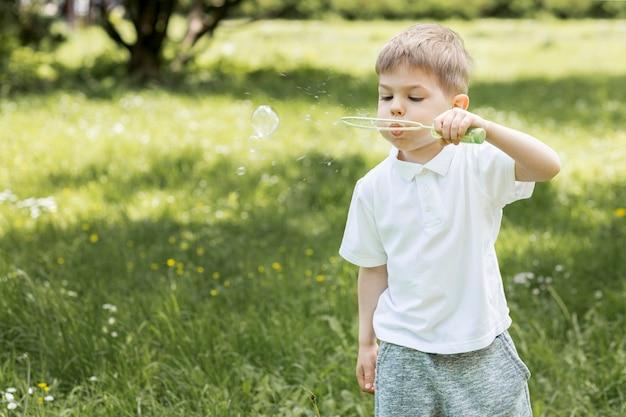 Garoto bonito, soprando bolhas no parque