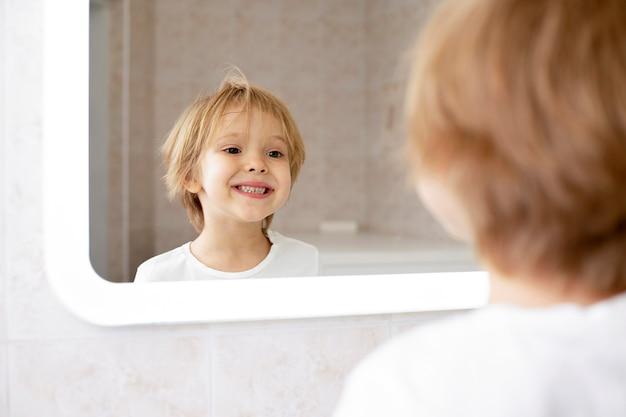 Garoto bonito sorrindo no espelho