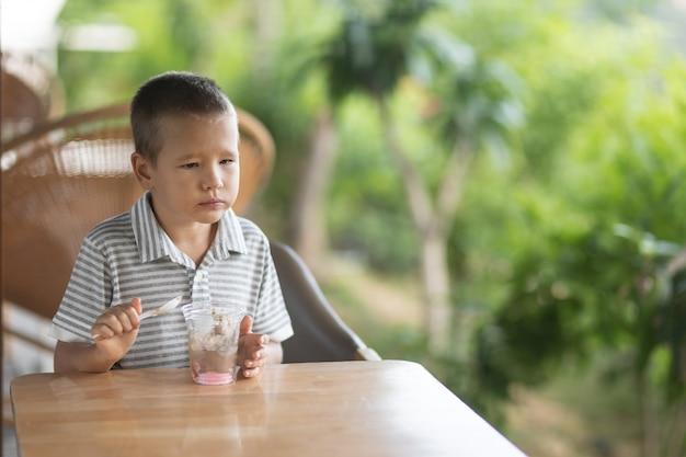 Garoto bonito tomando sorvete em um café ao ar livre