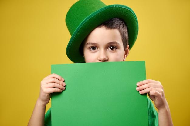 Garoto bonito vestido com um duende com um boné irlandês verde cobre o rosto com uma folha de papel verde com espaço de cópia