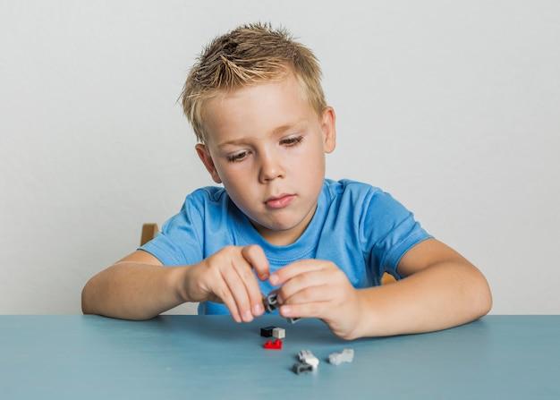 Garoto bonito vista frontal brincando com lego