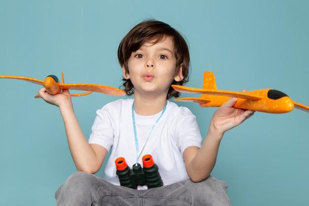 Garoto bonito vista frontal segurando aviões de brinquedo laranja em camiseta branca na mesa azul