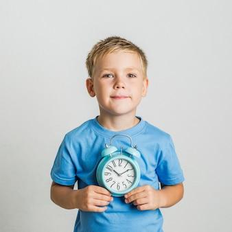 Garoto bonito vista frontal segurando um relógio