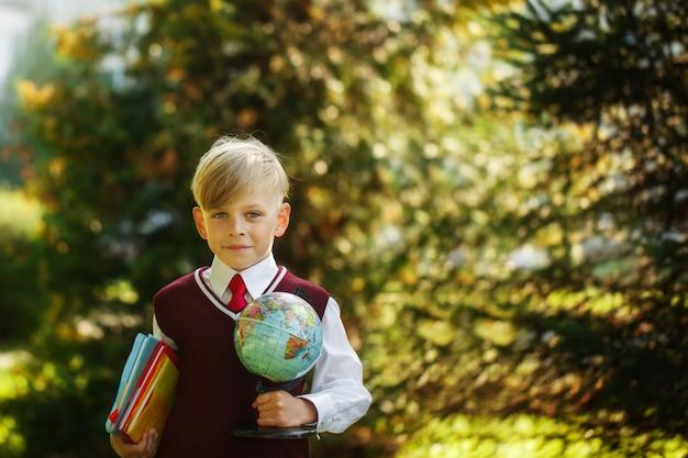 Garoto bonito voltar para a escola. criança com livros e globo no primeiro dia de escola.