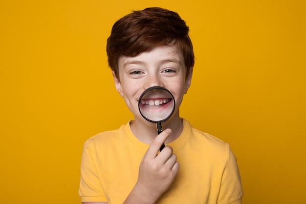Garoto branco gengibre está segurando uma lupa na boca e sorrindo para a câmera, posando na parede amarela do estúdio