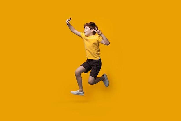Garoto branco gengibre pulando na parede amarela de um estúdio e fazendo uma selfie