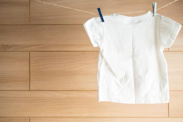 Garoto branco t-shirt de roupa pendurada no varal