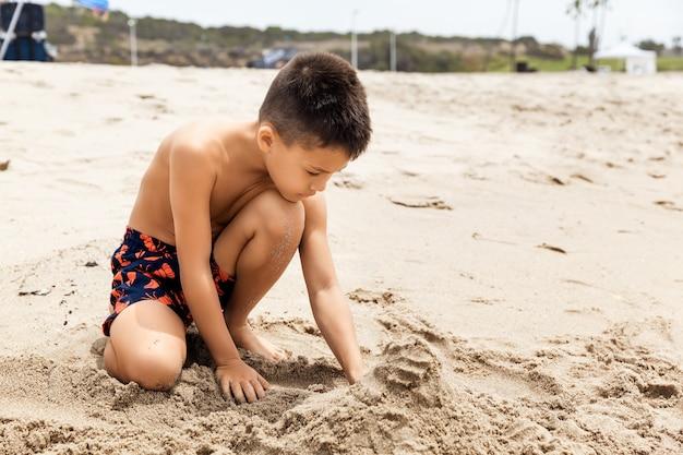 Garoto brincando com areia em uma praia tropical no conceito de férias, viagens e férias de verão