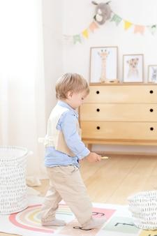 Garoto brincando com brinquedos no quarto. decoração de quarto infantil ecológica no escandinavo. retrato de um menino brincando no jardim de infância. quarto infantil e design de interiores. o garoto está em casa. garotinho