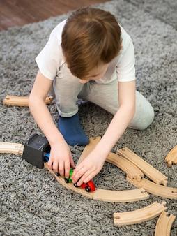 Garoto brincando com jogo de estradas e carros de madeira