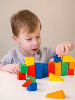 Garoto brincando com jogo de formas coloridas