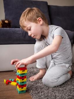 Garoto brincando com o jogo da torre de madeira colorida