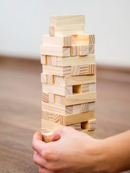 Garoto brincando com o jogo da torre de madeira