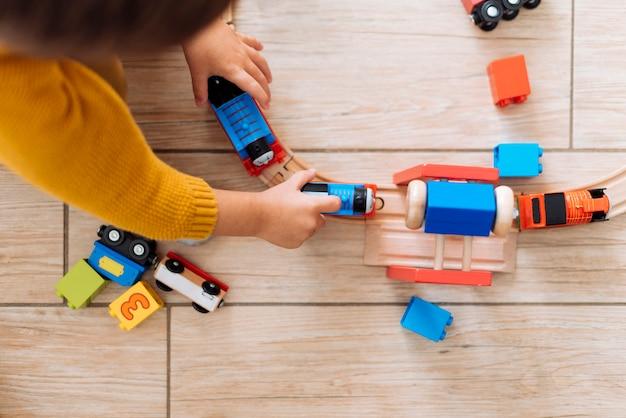 Garoto brincando com trem de brinquedo