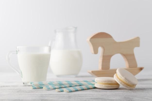 Garoto café da manhã com leite e macaroons de branco na mesa