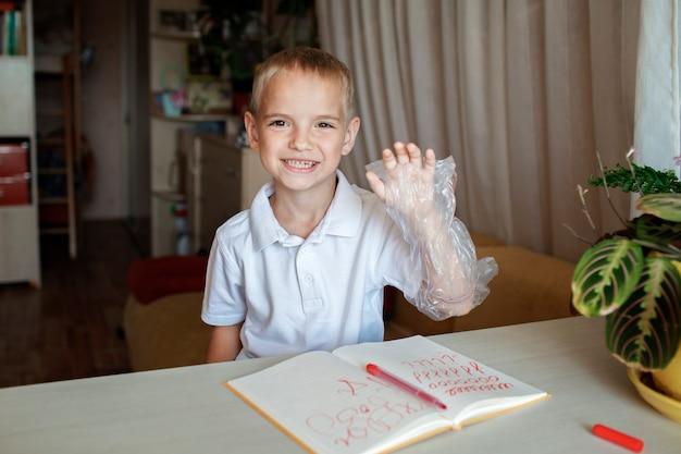 Garoto canhoto colocou a mão esquerda em uma luva de plástico para evitar confuso dia internacional do canhoto