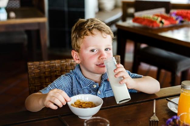Garoto caucasiano tomando café da manhã sozinho