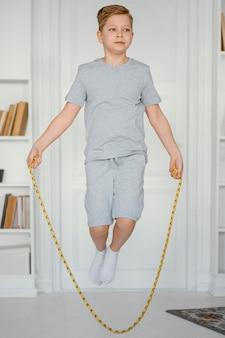 Garoto cheio de tiro pulando corda dentro de casa