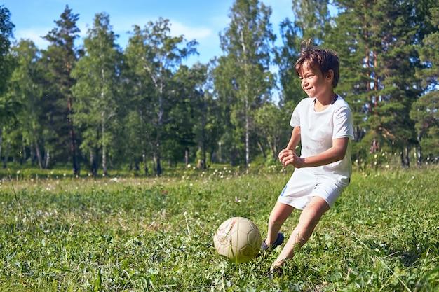 Garoto chutando uma bola de futebol no campo