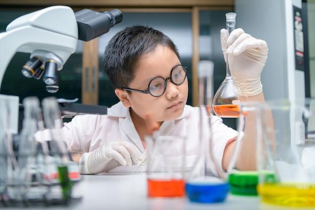 Garoto cientista fazendo experimento em laboratório químico,