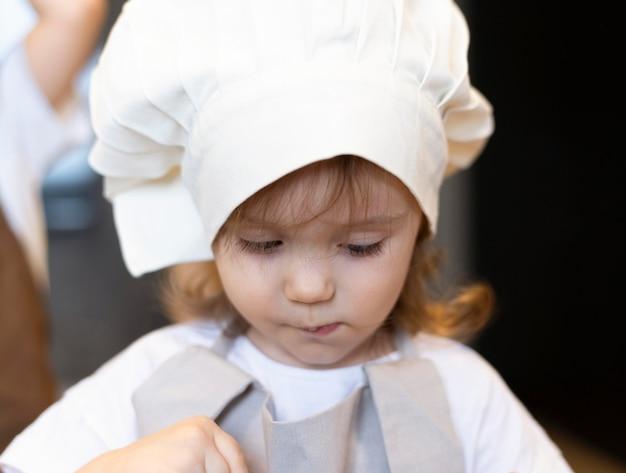Garoto close-up vestindo roupas de cozinheira