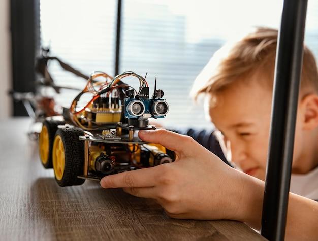 Garoto colocando robô na prateleira